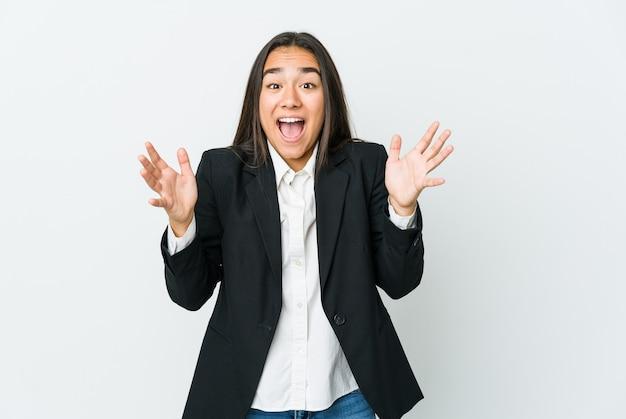 Jonge aziatische zakenvrouw die op witte muur wordt geïsoleerd die een overwinning of een succes viert, is hij verrast en geschokt