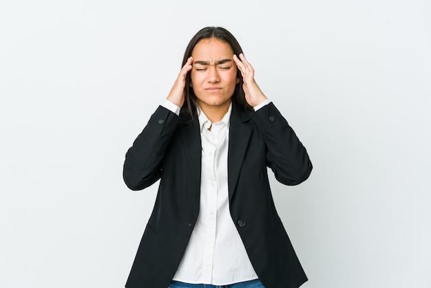 Jonge aziatische zakenvrouw die op witte muur wordt geïsoleerd die tempels aanraakt en hoofdpijn heeft