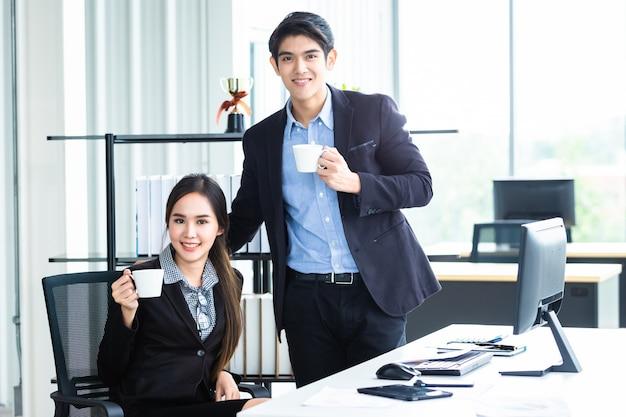 Jonge aziatische zakenvrouw en zakenman partners tijdens het samenwerken en ontspannen met een kopje koffie