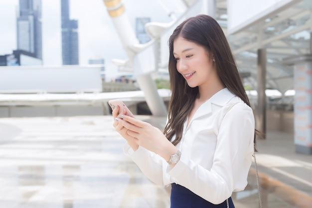 Jonge aziatische zakenvrouw gaat naar kantoor of werkplek waar ze een smartphone heeft