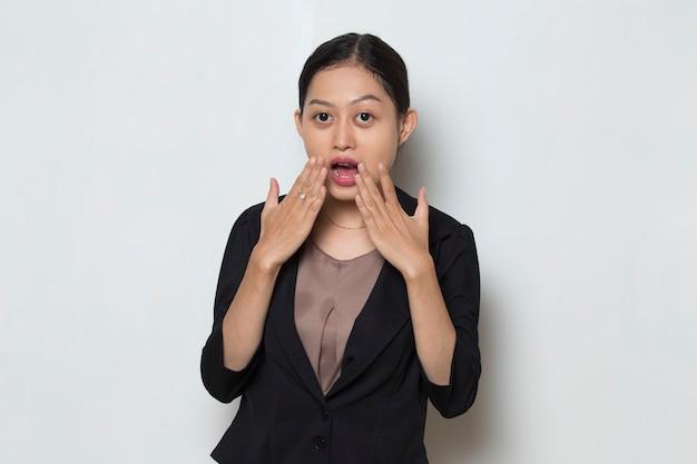 Jonge aziatische zakenvrouw geschokt die mond bedekt met handen?