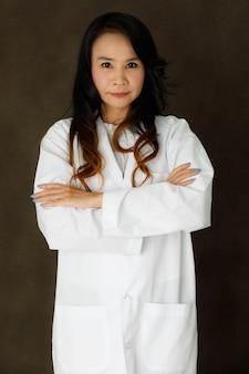 Jonge aziatische zakenvrouw in een elegante witte jurk die naar de camera kijkt en lacht tegen een donkergrijze achtergrond