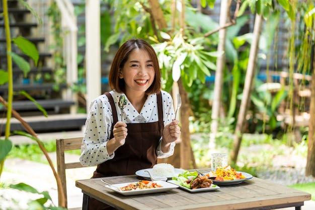 Jonge aziatische zakenvrouw is eigenaar van een coffeeshop en beveelt het voedselmenu aan dat in de winkel verkrijgbaar is
