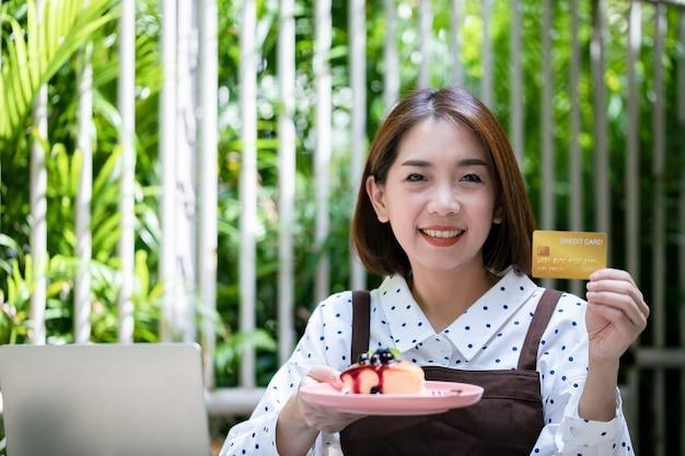 Jonge aziatische zakenvrouw is eigenaar van een coffeeshop, met een blauwe bessencake en een creditcard om klanten te vertellen dat ze voor de dienst moeten betalen