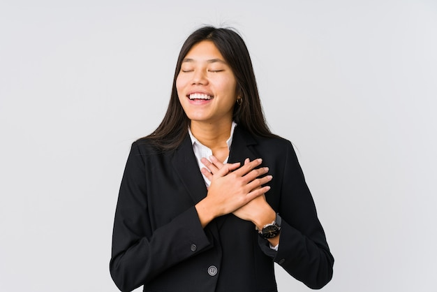 Jonge aziatische zakenvrouw lachen houden handen op hart, concept van geluk.