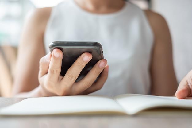 Jonge aziatische zakenvrouw met behulp van mobiele telefoon in office, vrouw zitten en hand scherm op mobiel aan te raken