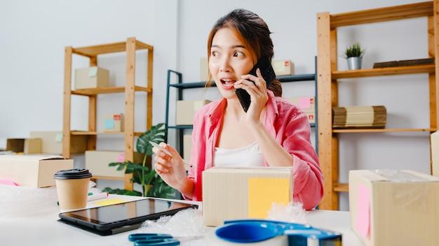 Jonge aziatische zakenvrouw met behulp van mobiele telefoon oproep ontvangen van inkooporder en product op voorraad controleren, thuiskantoor werken. kleine ondernemer, online marktlevering, freelance lifestyleconcept.