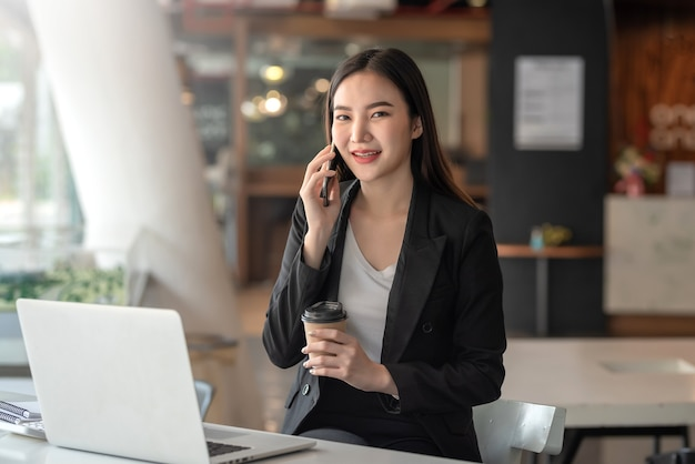 Jonge aziatische zakenvrouw met een koffiekopje praten aan de telefoon. kijken naar een camera op kantoor.