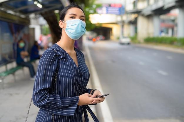 Jonge aziatische zakenvrouw met masker denken tijdens het gebruik van telefoon bij de bushalte