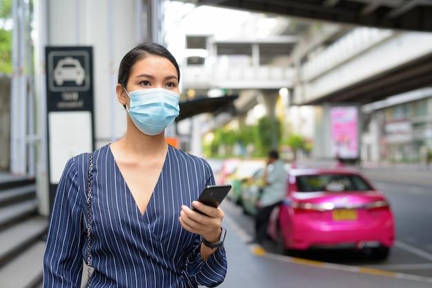 Jonge aziatische zakenvrouw met masker denken tijdens het gebruik van telefoon op het taxistation in de straten van de stad