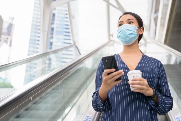 Jonge aziatische zakenvrouw met masker die telefoon gebruikt terwijl ze onderweg koffie drinkt als het nieuwe normaal tijdens covid-19