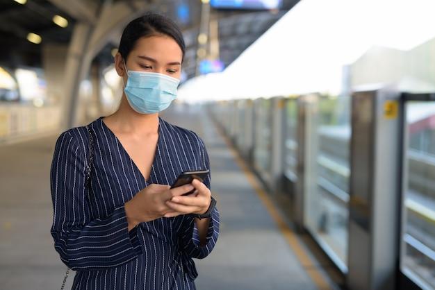 Jonge aziatische zakenvrouw met masker met behulp van telefoon op het skytrain-station