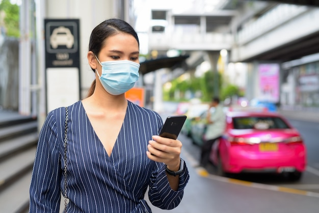 Jonge aziatische zakenvrouw met masker met behulp van telefoon op het taxistation in de straten van de stad