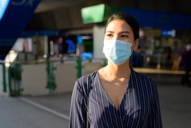 Jonge aziatische zakenvrouw met masker voor bescherming tegen de uitbraak van het coronavirus die wegloopt van het treinstation