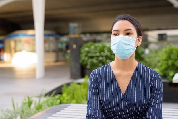 Jonge aziatische zakenvrouw met masker voor bescherming tegen uitbraak van het coronavirus, denken en zitten in de stad