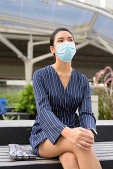 Jonge aziatische zakenvrouw met masker zitten en denken in de stad