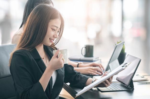 Jonge aziatische zakenvrouw ontspannen met koffie