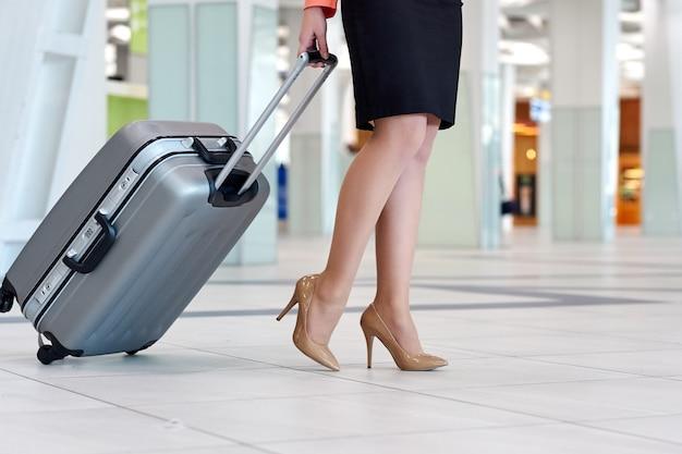 Jonge aziatische zakenvrouw op de luchthaven met trolley close-up