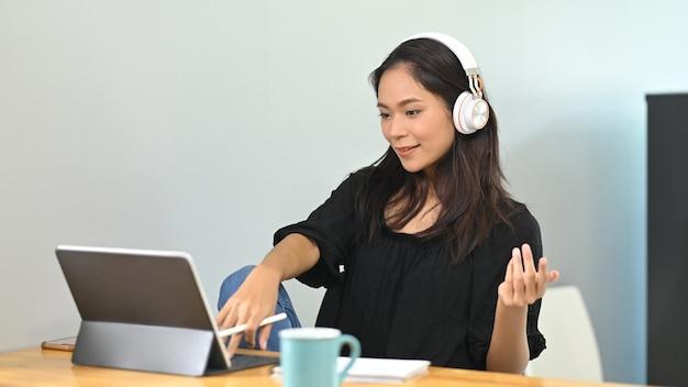 Jonge aziatische zakenvrouw thuis werken en virtuele videoconferentie bijeenkomst met collega's uit het bedrijfsleven.