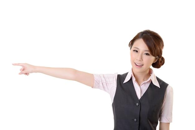 Jonge aziatische zakenvrouw wees ergens, close-up portret op witte muur.