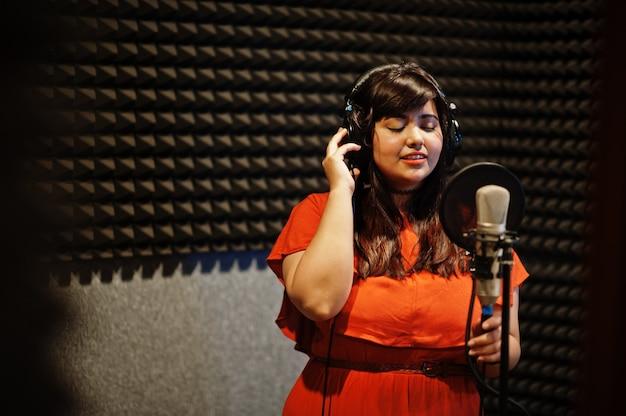 Jonge aziatische zangeres opnemen in de studio