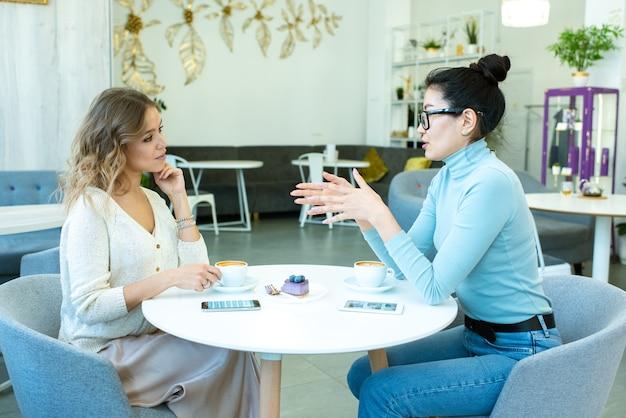 Jonge aziatische zelfverzekerde ondernemers een van de werkpunten uit te leggen aan haar collega door kopje koffie in café