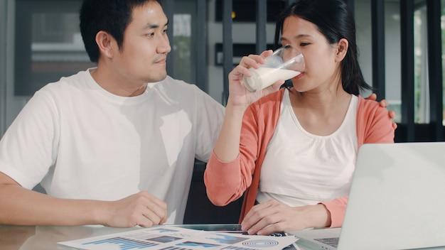 Jonge aziatische zwangere vrouw die laptop verslagen van inkomsten en uitgaven thuis gebruikt. papa geeft zijn vrouw melk terwijl recordbudget, belasting, financieel document 's morgens in de huiskamer werkt.