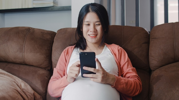 Jonge aziatische zwangere vrouw met behulp van mobiele telefoon zoeken zwangerschap informatie. mamma die het gelukkige positief en vreedzame glimlachen voelen terwijl zorg haar kind thuis liggend op bank in woonkamer.