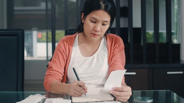 Jonge aziatische zwangere vrouw records van inkomsten en uitgaven thuis. mammameisje gelukkige gebruikende laptop verslagbegroting, belasting, financieel document, elektronische handel die in woonkamer thuis werken.