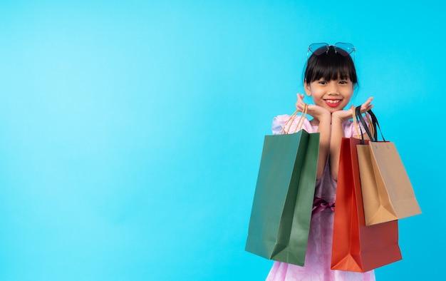 Jonge azië meisjesjong geitje het winkelen zak