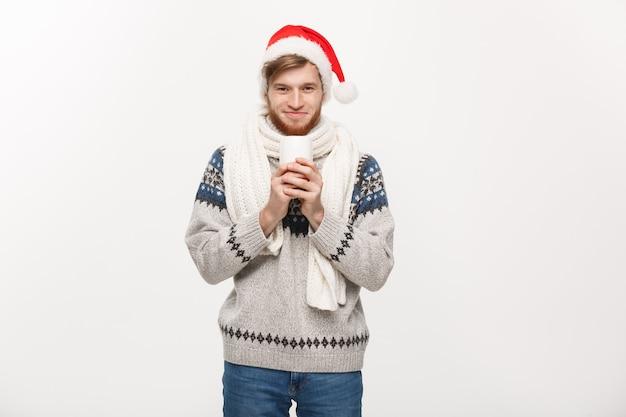 Jonge baardmens in sweater en santahoed die een hete koffiekop houden die op wit wordt geïsoleerd
