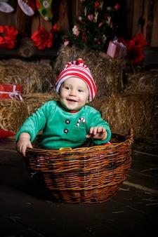 Jonge baby die het leuke uitrusting stellen voor portretten in de studiozitting draagt binnen een mand met een deken