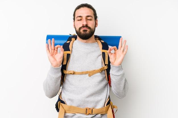 Jonge backpacker man geïsoleerd op wit ontspant na een zware werkdag, ze presteert yoga.