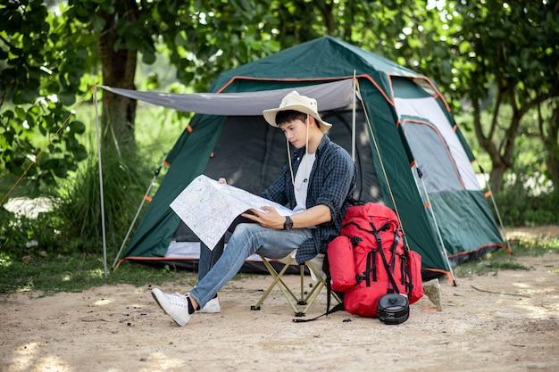 Jonge backpacker man met hoed zit aan de voorkant van de tent in het natuurbos en kijkt op een papieren kaart van bospaden om te plannen tijdens het kamperen op zomervakantie, kopieer ruimte