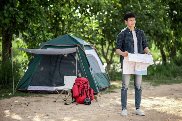 Jonge backpacker man staat en houdt een papieren kaart in de hand voor de tent in het natuurbos en kijkt met een glimlach uit naar bospaden om te plannen tijdens het kamperen op zomervakantie, kopieer ruimte