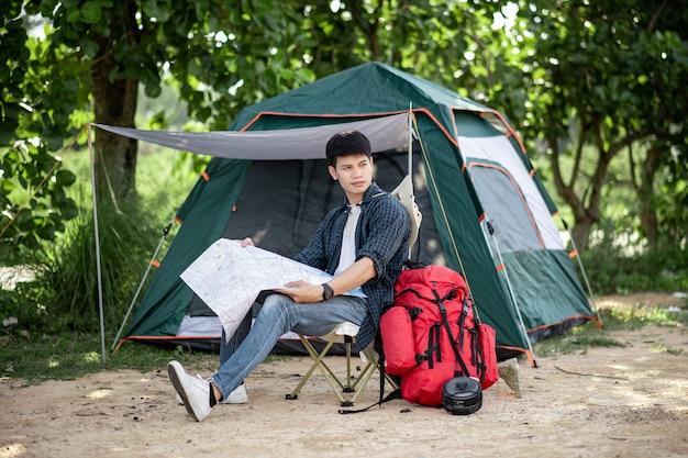 Jonge backpacker man zit aan de voorkant van de tent in het natuurbos en kijkt op een papieren kaart van bospaden om te plannen tijdens het kamperen op zomervakantie, kopieer ruimte