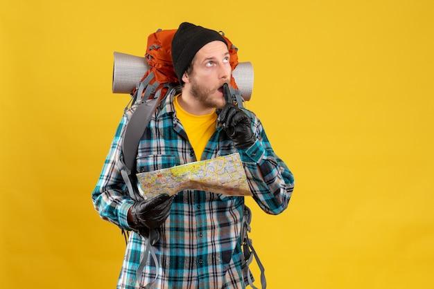 Jonge backpacker met leren handschoenen die een kaart vasthoudt en aan iets denkt