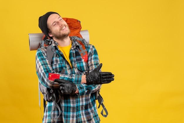 Jonge backpacker met zwarte hoed met creditcard die hand geeft