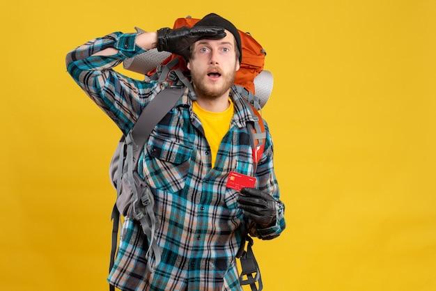 Jonge backpacker met zwarte hoed met creditcard observeren