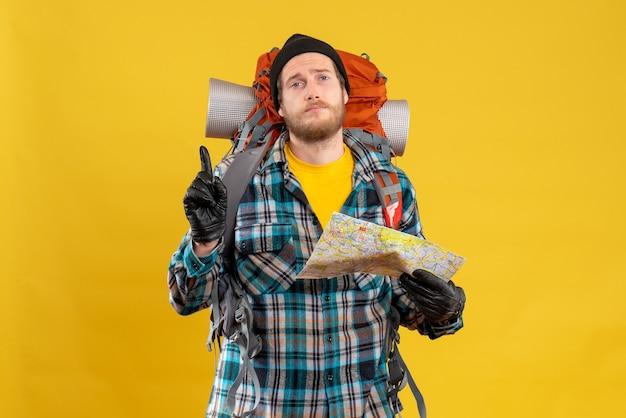 Jonge backpacker met zwarte hoed met kaart wijzend met vinger omhoog