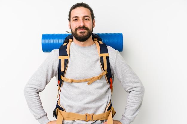 Jonge backpackermens die op een witte muur wordt geïsoleerd die zeker handen op heupen houdt.