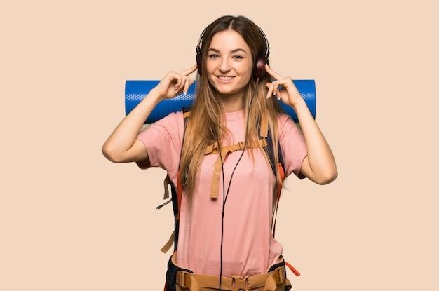 Jonge backpackervrouw die aan muziek met hoofdtelefoons op gele muur luisteren