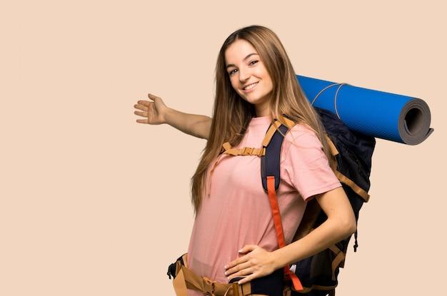 Jonge backpackervrouw die achteruit en een product op geïsoleerde gele achtergrond richten richten