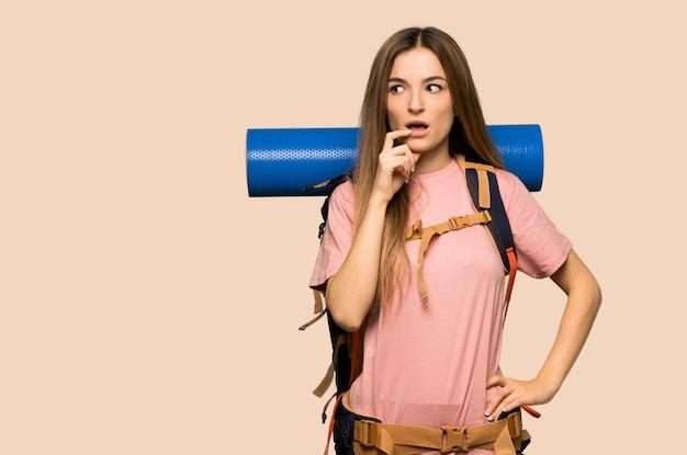 Jonge backpackervrouw die twijfels hebben terwijl omhoog het kijken