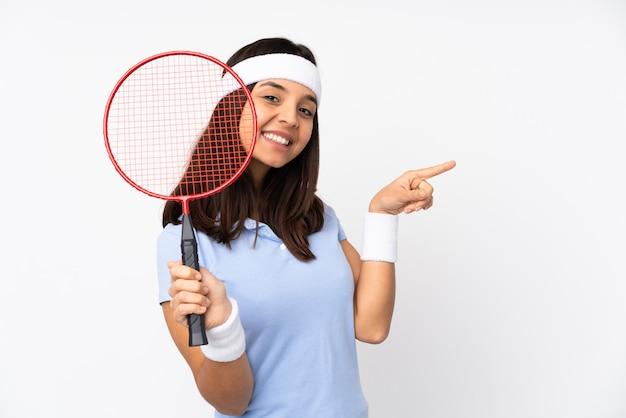 Jonge badmintonspeler vrouw over geïsoleerde witte achtergrond wijzende vinger naar de zijkant