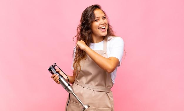Jonge bakker die zich gelukkig, positief en succesvol voelt, gemotiveerd wanneer ze voor een uitdaging staat of goede resultaten viert