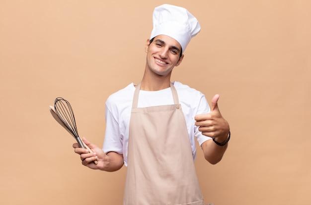 Jonge bakker die zich trots, zorgeloos, zelfverzekerd en gelukkig voelt, positief glimlachend met duimen omhoog