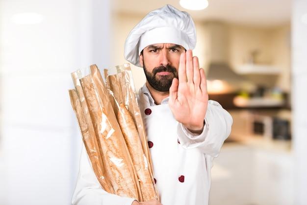Jonge bakker met wat brood en stopteken in de keuken