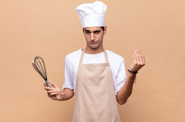 Jonge bakkersman die capice of geldgebaar maakt en u zegt uw schulden te betalen!