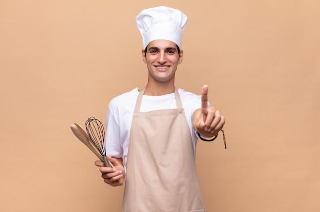 Jonge bakkersman die trots en zelfverzekerd glimlacht en nummer één triomfantelijk laat poseren, zich als een leider voelt